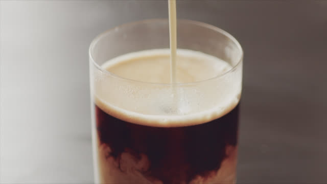 4K slow motion video of pouring milk in coffee