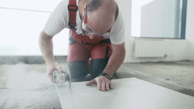 Slow motion video of professional tiler cutting tile