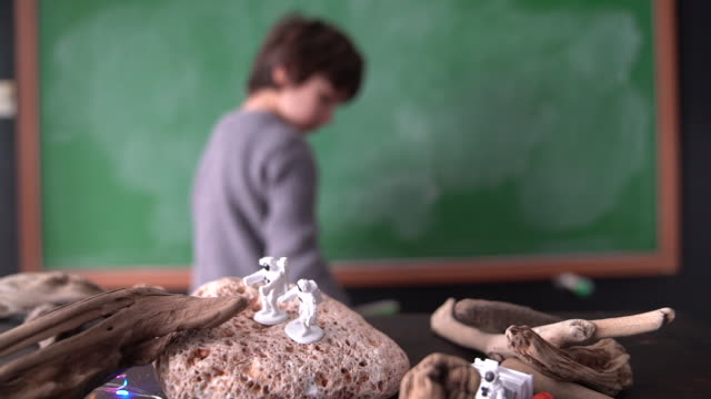 HD Slow Motion Video Of School Boy Playing With Scientific Toys In Front Of Green Chalkboard video