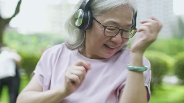 Slow motion video of senior woman listening to music and dancing