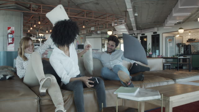 Slow motion video of three  colleagues pillow fighting together at the office during a break
