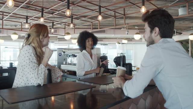 Slow motion video of three colleagues taking a coffee break in their modern coworking space video