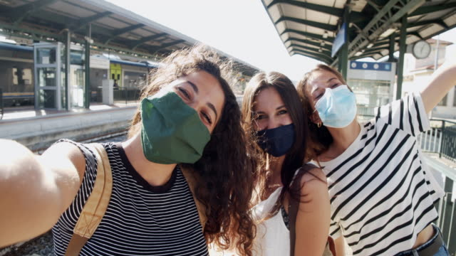 Slow motion video of three friends taking a selfie together - Pov view Slow motion video of three friends taking a selfie together - Pov view. They are in a train station, wearing protective facemasks. station stock videos & royalty-free footage