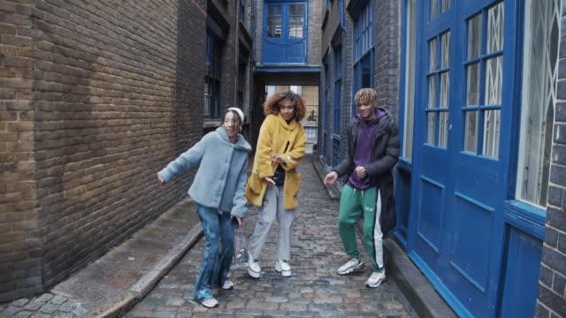 vidéos et rushes de vidéo au ralenti de trois amis heureux dansant ensemble dans la ville - mode londres