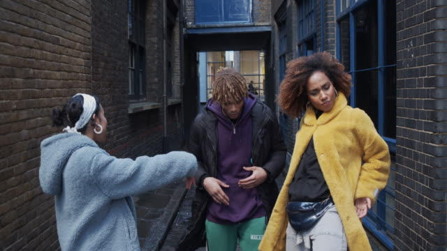 Slow motion video of three hip friends dancing together outdoor in the city video