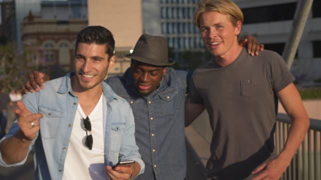 vídeos y material grabado en eventos de stock de slow motion video de tres amigos varones multiétnicas visiten la ciudad - ocio