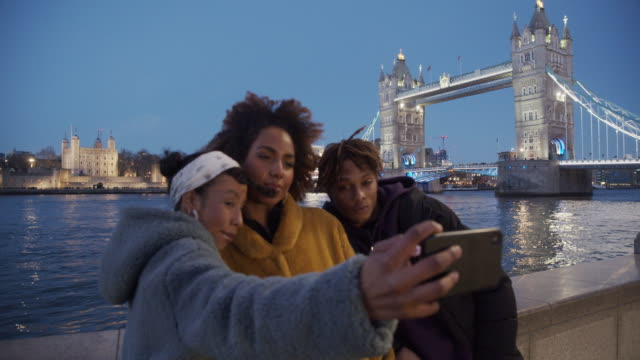 Slow motion video of three young adult hip friends taking a selfie in London near Tower Bridge - Focus on background, on the Tower Bridge
