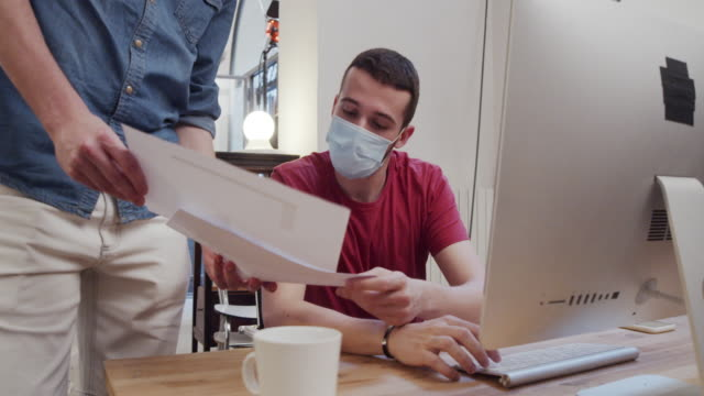 Slow motion video of two colleagues while they are working together in the office, wearing protective face masks video