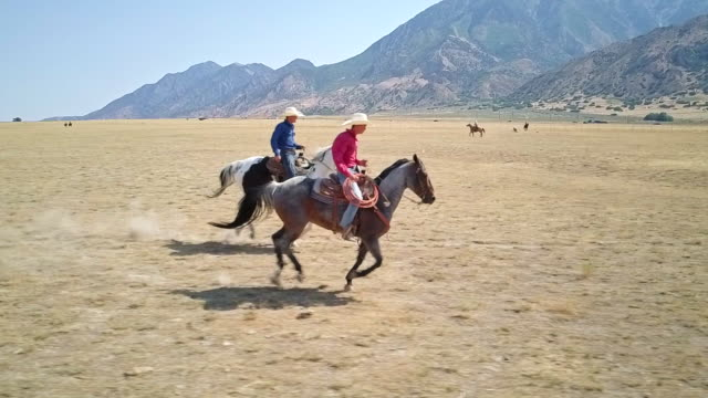 Slow motion video of two cowboys horseback riding together video