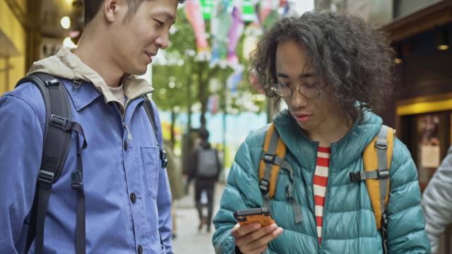 レストランへの方向のために携帯電話を見ている2人の友人のスローモーションビデオ - 方向点の映像素材/bロール