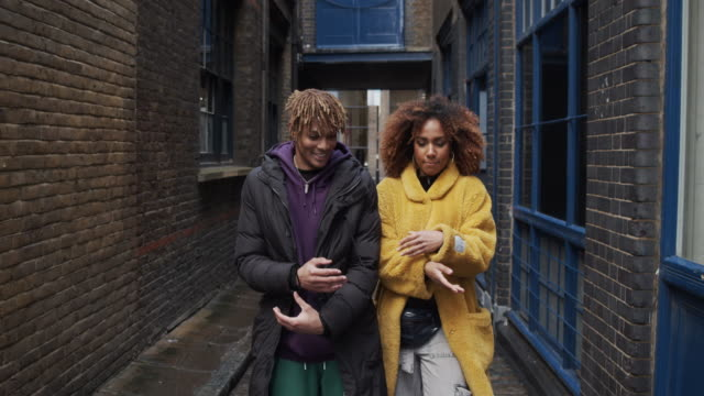 Slow motion video of two hip friends dancing together outdoor in the city video