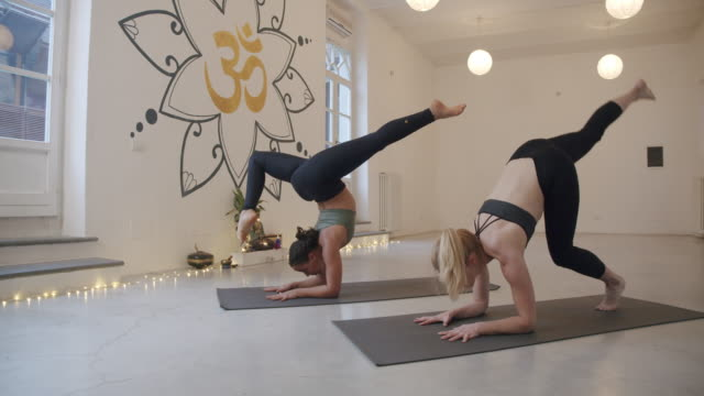 Slow motion video of two women practicing yoga together