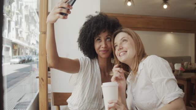 vídeos de stock, filmes e b-roll de vídeo em câmera lenta de duas jovens adultas tirando uma selfie juntas no café - amizade feminina