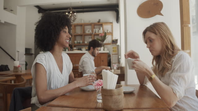 Slow motion video of two young adult women together at the cafe video