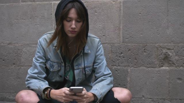 bin yıllık kadın cep telefonunda bir mesaj yazarak slow motion video - kapüşon stok videoları ve detay görüntü çekimi
