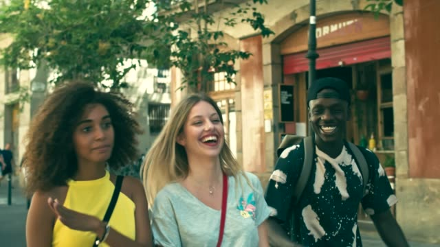 slow motion video of young millennials friends having fun in the city - tre persone video stock e b–roll