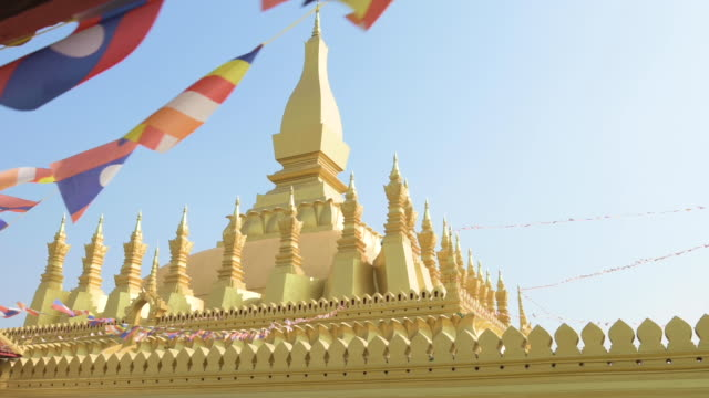 (Selective focus) Slow motion video os Laos flags waving in the foreground with the beautiful Pha That Luang in the background. Pha That Luang is a gold-covered large Buddhist stupa in the centre of the city of Vientiane, Laos.