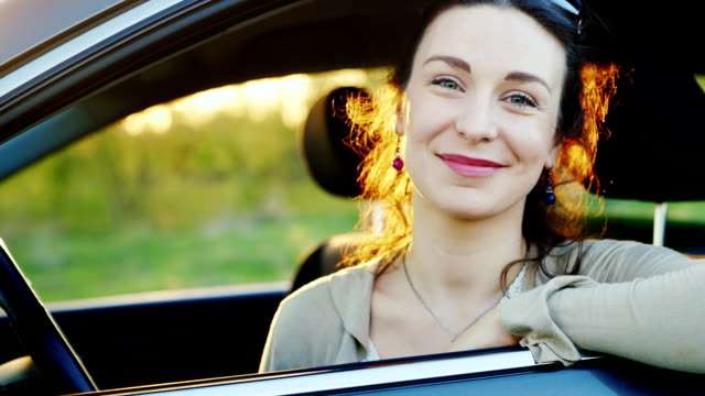 Slow motion video portrait of a young female driver. Looks through the window to the camera, smiling video