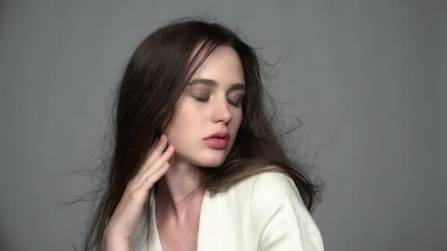 медленное движение видео портрет красоты молодой брюнетки женщина с зелеными глазами и потокового волос - white background стоковые видео и кадры b-roll