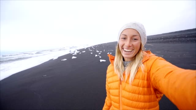 Slow motion Video selfie portrait of young woman standing at black sand beach in Iceland video