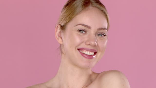 Slow motion video shot of smiling beautiful girl, isolated on pink background. Bare shoulders