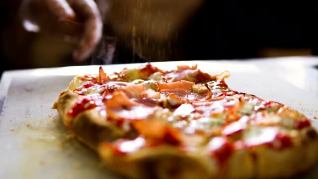 slow motion video. the hand of the chef sprinkles spices on the pizza - decorazione per dolci video stock e b–roll