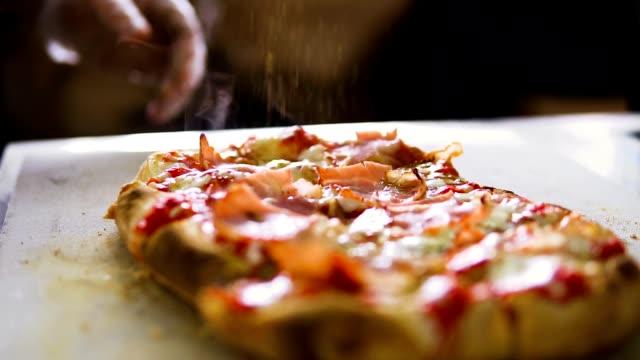 slow motion-video. kocken strössel kryddor på pizza - confetti bildbanksvideor och videomaterial från bakom kulisserna