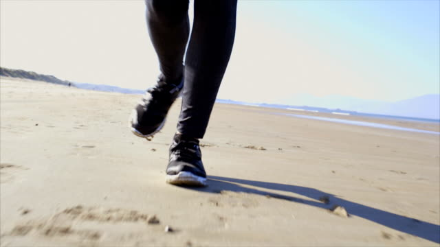 Slow motion video woman's feet jogging on beach video