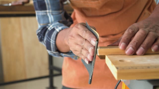 slow motion view: hands of a male carpenter sanding wooden plate in the workshop - carta vetrata video stock e b–roll
