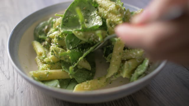 slow motion view of eating spinach penne pasta salad with green pesto sauce