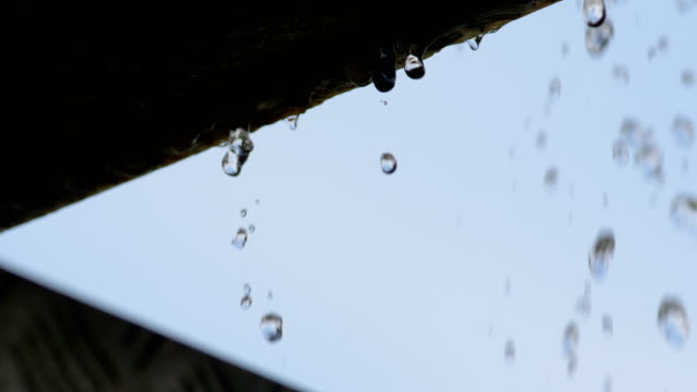 Slow motion: water drop fall from eaves in close up video