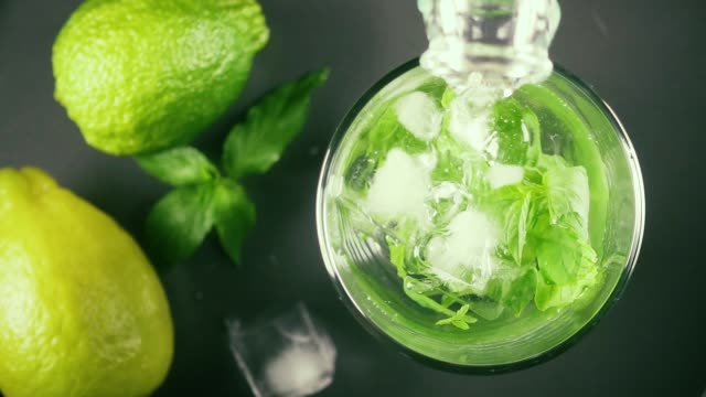 Slow motion water from a bottle in a glass of mint and ice top view