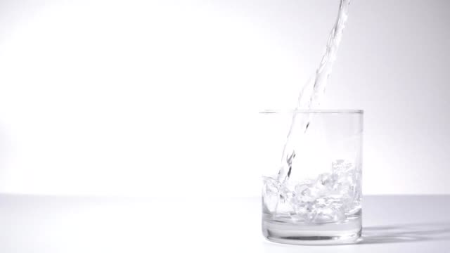 slow motion: water pouring into drinking glass - bicchiere vuoto video stock e b–roll