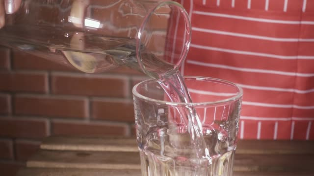 slow motion water pours from the decanter into a glass of female hands - decanter video stock e b–roll