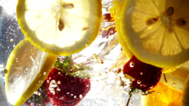 vídeos de stock e filmes b-roll de slow motion whirlpool with sliced lemon and strawberry - strawberry