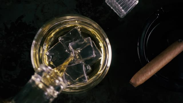 slow motion whiskey in a glass and cigar - rum superalcolico video stock e b–roll