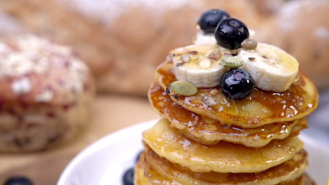 HD Slow motion wide shot pouring honey or maple syrup on stack of homemade fresh butter pancakes topping with blueberry and sliced banana on white plate for breakfast. Delicious sweet food or dessert.