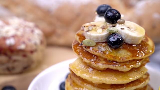 hd slow motion weitschuss gießen honig oder ahornsirup auf stapel von hausgemachten frischen butter pfannkuchen topping mit heidelbeere und geschnittene banane auf weißem teller zum frühstück. köstlichesüße speisen oder desserts. - brunch stock-videos und b-roll-filmmaterial
