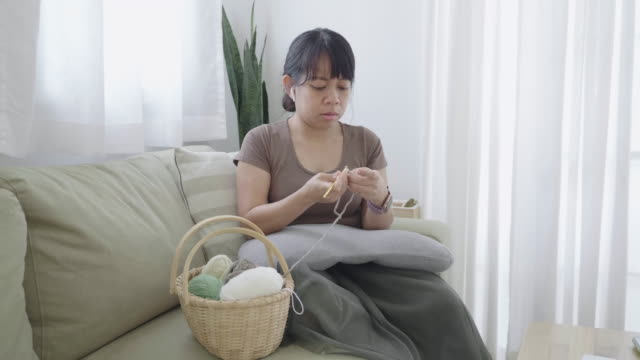 slow motion - woman crocheting in a living room - auricolari wireless video stock e b–roll