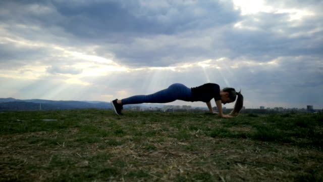 Bидео Slow Motion Woman doing Push ups, press ups exercise young woman.  Exercising at park silhouette. Fit young woman doing training workout Slow Motion.