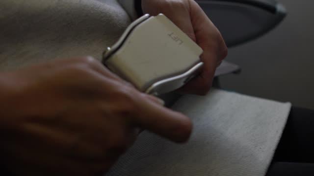 Slow Motion woman fastening seat belt plane. Passengers wearing safety belt