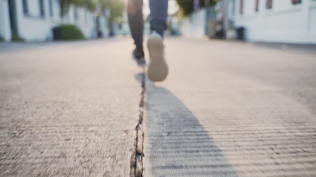Slow motion: Woman feet running on road, Len flare Steadicam shot video