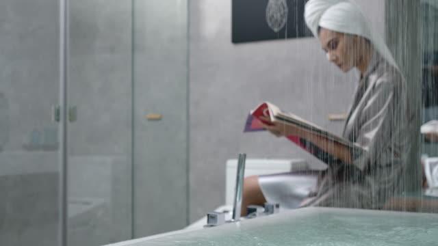 stockvideo's en b-roll-footage met 4k slow motion vrouw in vorm slijtage zijden pyjama zittend lezen in de buurt van het bad - woman home magazine