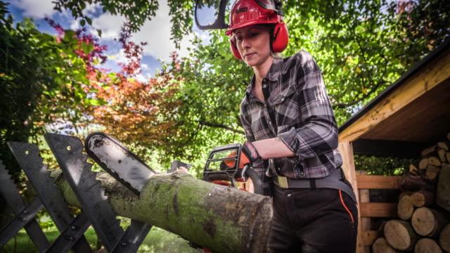 zeitlupe: frau sägt brennholz mit kettensäge - brennholz stock-videos und b-roll-filmmaterial