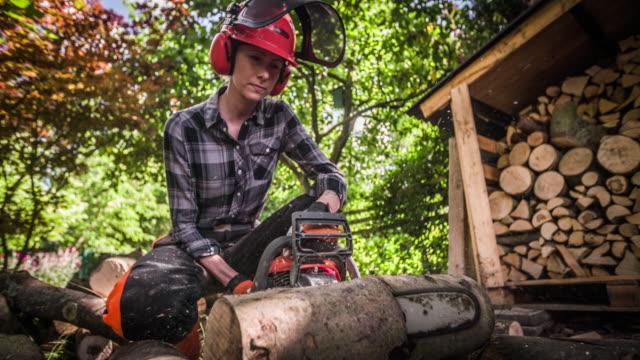 yavaş hareket: elektrikli testere ile ağaç gövdesi ni gören kadın - şömine odunu stok videoları ve detay görüntü çekimi