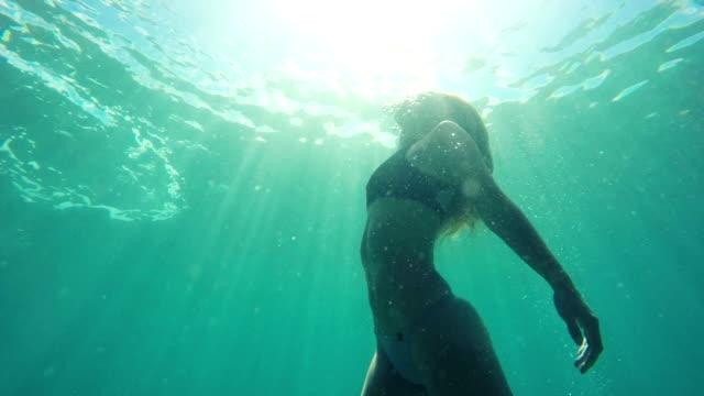 rallentatore donna nuoto verso superficie subacqueo con bellissimi bagliori del sole a rallentatore - sotto video stock e b–roll
