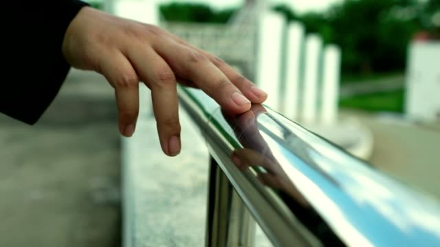 slow motion: woman walking and holding hands with an iron railing relaxed mood - mindfulness stock videos & royalty-free footage