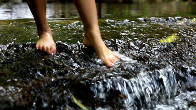 slow motion, woman walking relaxation in waterfalls - fare un passo video stock e b–roll
