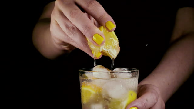 slow motion. women's hands squeeze a slice of lemon - сжимать стоковые видео и кадры b-roll