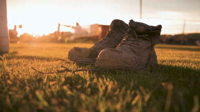 vidéos et rushes de bottes boueuses d'ouvriers de mouvement lent près d'un chantier de construction devant un coucher du soleil - bottes